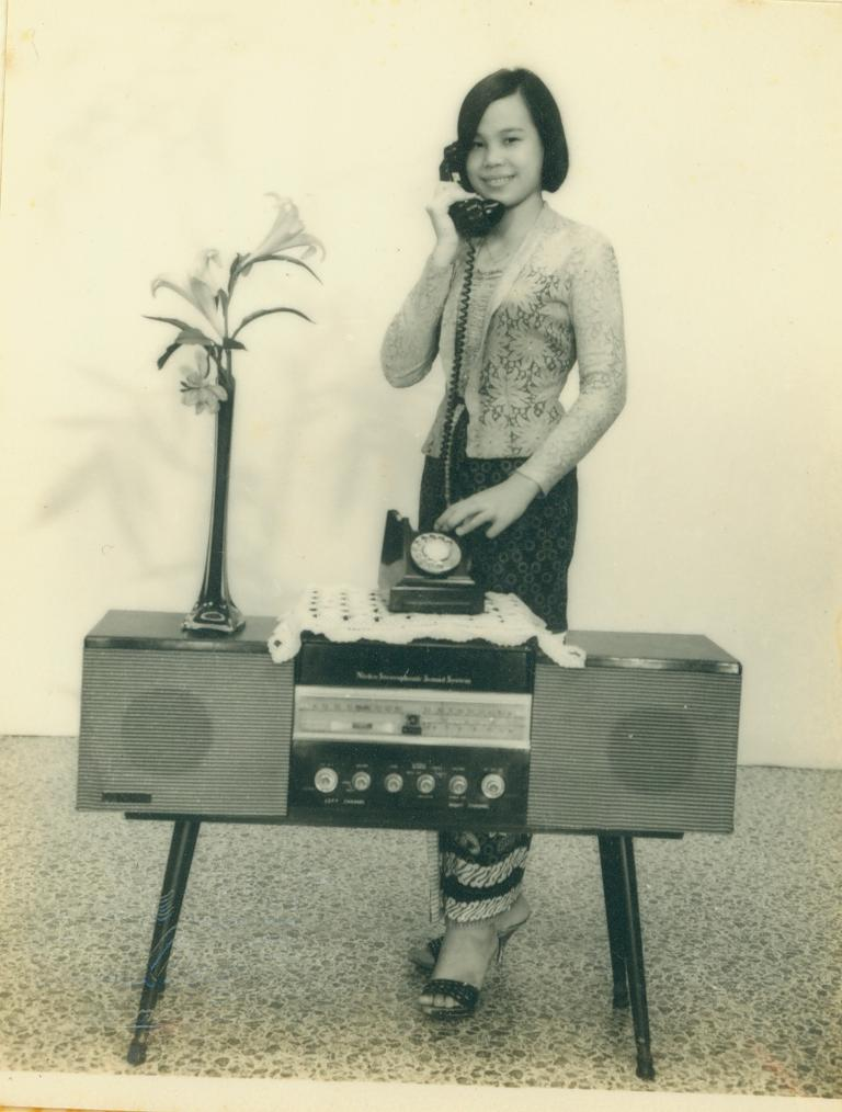 A lady posing with a radio and telephone. Photo Seow Shin Horng