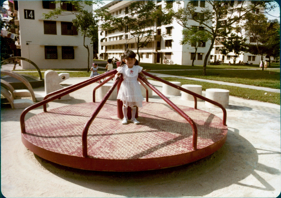 "A child at a playground with the ""chek lau"" flats in the background. Photo: Lim Poh Kwan"