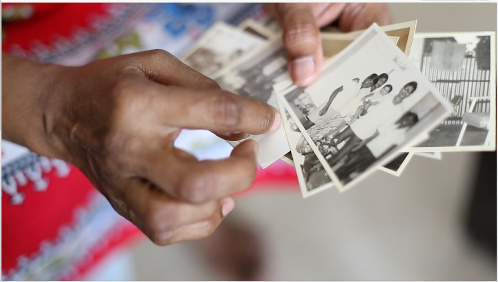Mdm Saraswathi with a stack of old photographs of Seletar Camp in her hands. Photo credit: SG Snaps