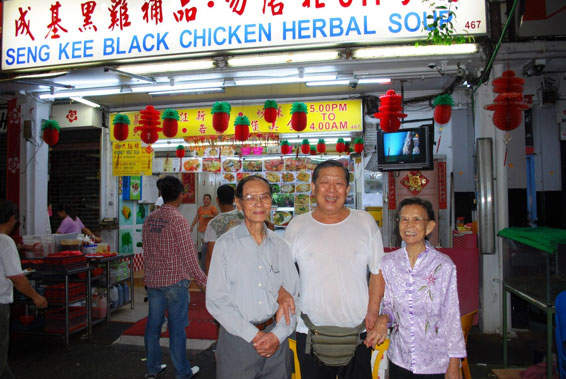 2012 photo taken at the site of the former studio, showing Mr. Kuet and his wife together with the owner of the current shop.